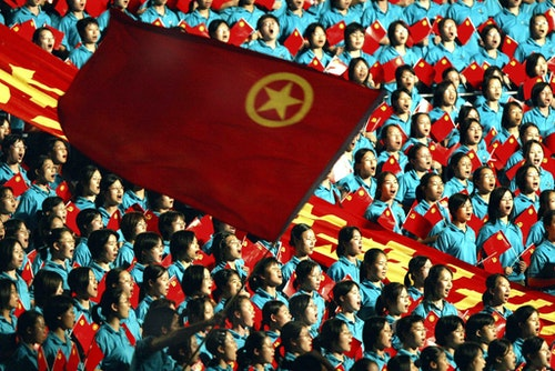 Chinese youths sing a patriotic song under a flag of the Communist Youth League at a party to mark t..