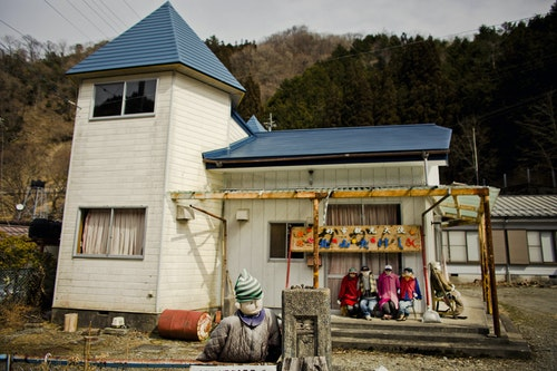 Scarecrows sit in front of a house in the mountain village of Nagoro