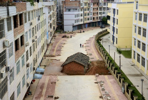 """A """"nail house"""", the last building in the area, sits in the middle of a road under construction in Nanning"""