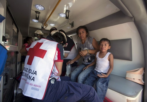 A Red Cross paramedic treats a woman and a child experiencing shock outside the jail during a clash of rival groups in the prison of Cancun