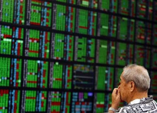 A man looks at stock market monitors inside a bank in Taiwan