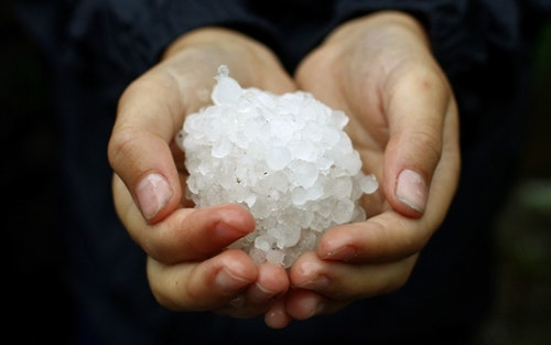 A youngster shows off a ball made from hail stones in south London