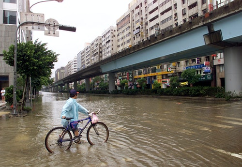 A BICYCLIST MAKES HIS WAY THROUGH A FLOODED STREET IN TAIPEI.