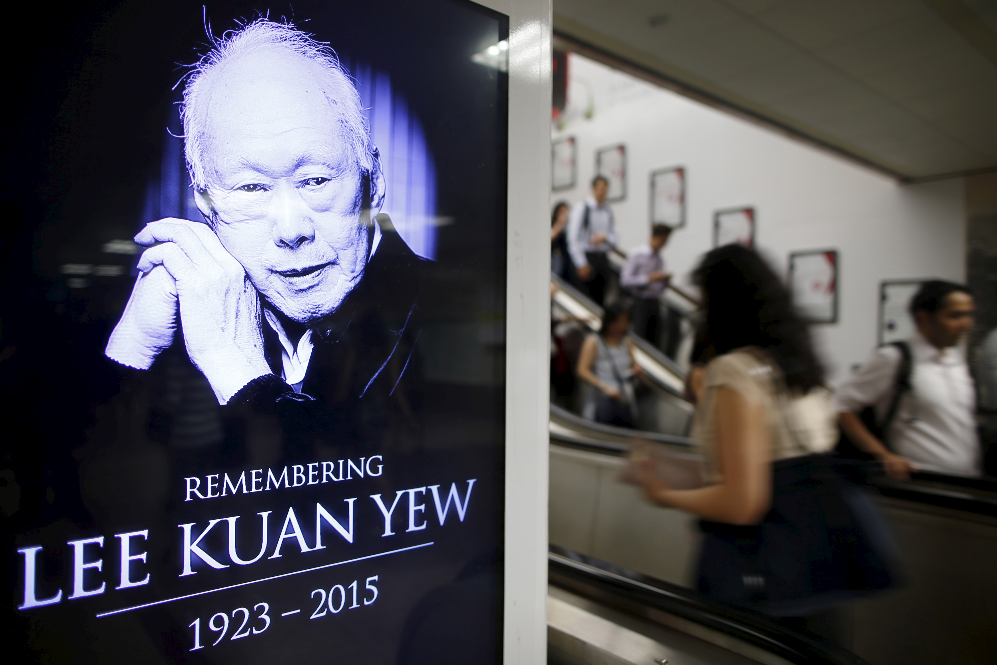 Commuters pass by a signboard displaying a tribute to the late first prime minister Lee Kuan Yew in a train station at the central business district in Singapore