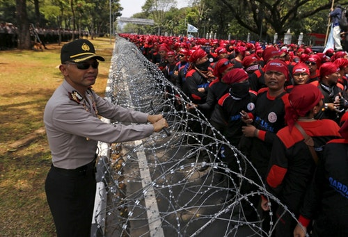 Central Jakarta police chief Hendro Pandowo stands next to razor wire as Indonesian trade union workers hold a protest outside the Presidential Palace in Jakarta