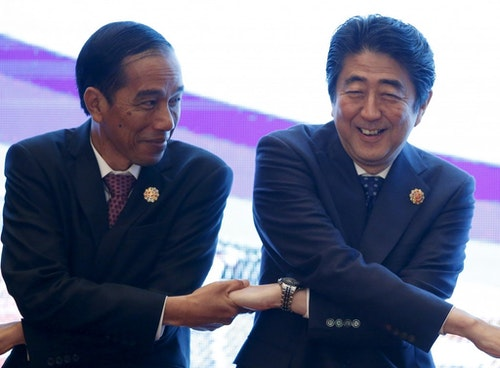 Indonesia's President Widodo links hands with Japan's PM Abe during the 27th ASEAN summit in Kuala Lumpur