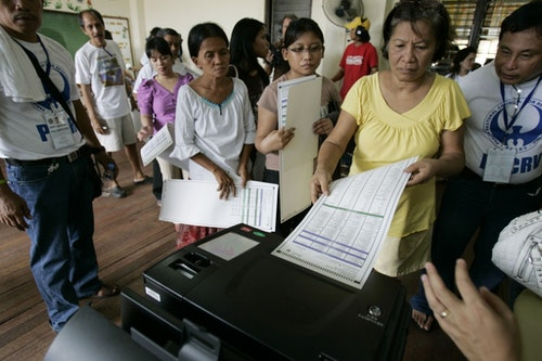 Filipinos wait in line to scan their ballots inside a counting machine at a voting center in San Juan, east of Manila, Philippines on Monday May 10, 2010. About 50 million Filipinos will vote Monday to elect a new president, vice-president and officials to fill nearly 18,000 national and local post in the country's first ever automated elections. (AP Photo/Aaron Favila)