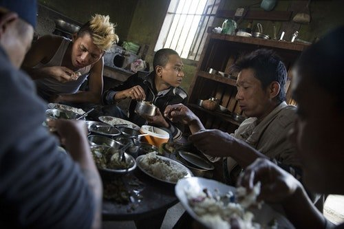 MYITKYINA, BURMA - JANUARY 26: Pat Jasan members and detainees share a meal on January 26, 2016 in Myitkyina, Burma. Pat Jasan is a Christian anti-drug group in Kachin State claiming over 100,000 members. Dissatisfied with the government's response towards widespread heroin use and poppy growing, the religious organization has taken matters into their own hands, organizing patrols, raiding houses, detaining drug dealers and users, and clearing poppy fields. Their brand of vigilante justice has been labeled extreme with some chapters accused of publicly beating those involved in the drug trade. (Photo by Taylor Weidman/Getty Images)