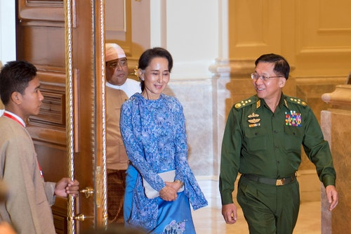 Aung San Suu Kyi (C) and Myanmar Military Chief Senior General Min Aung Hlaing arrive (R) for the handover ceremony from outgoing President Thein Sein and new Myanmar President Htin Kyaw at the presid