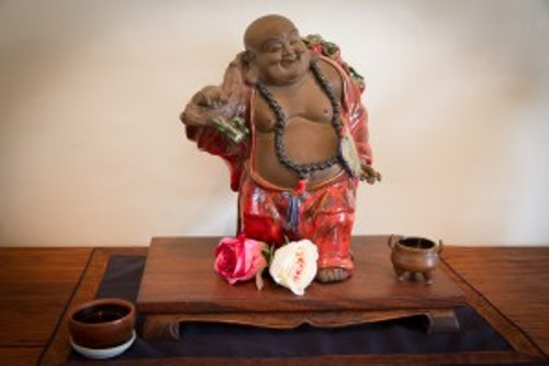 laughing Buddha with a cup of tea