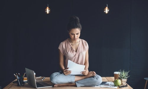 Focused african american businesswoman sitting in lotus pose with papers on table with laptop in office — Photo by alebloshka