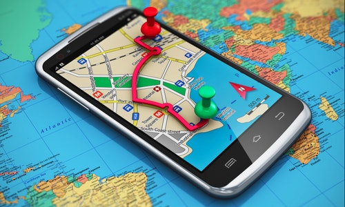 Mobile GPS navigation, travel and tourism concept: macro view of modern black glossy touchscreen smartphone with GPS navigation application, magnetic compass, pen and group of pushpins on world map wi