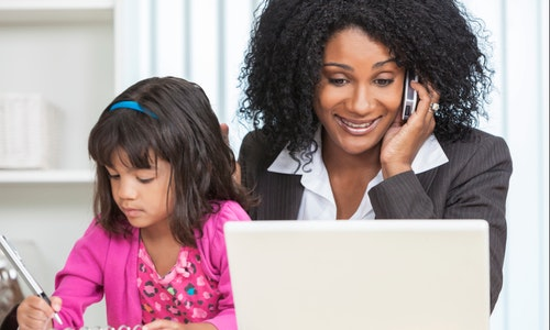Beautiful middle aged African American woman or businesswoman working on her cell phone & laptop computer and looking after her female child daughter
