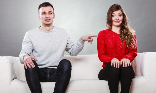 Shy woman and man sitting on sofa couch next each other. First date. Attractive girl and handsome guy meeting dating and trying to talk. Male touching picking up female.