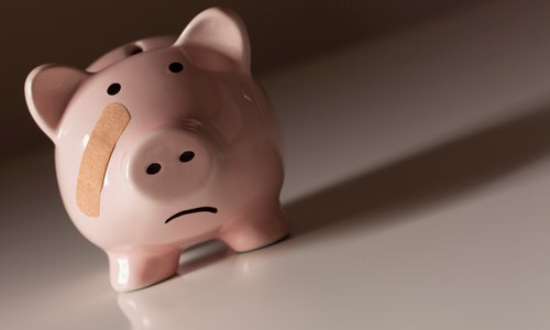 Piggy Bank with Bandage on Face on Dramatic Gradated Background.
