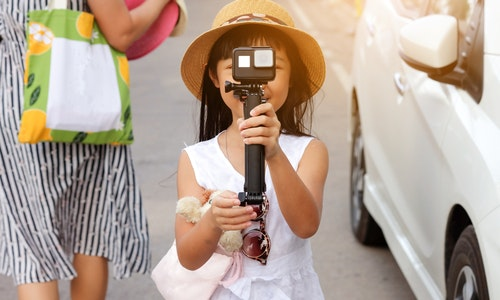 Asian child girls tourists are using action cam to record events while she is traveling to go to social media. - 圖片