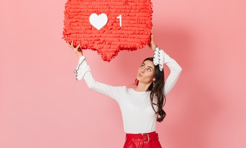 """Portrait of girl with interest looking at huge """"""""like"""""""" sign from Instagram. Brunette in red skirt posing on pink background"""