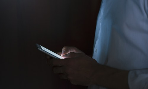 Close-up portrait of young handsome man using smart phone in hand on dark background